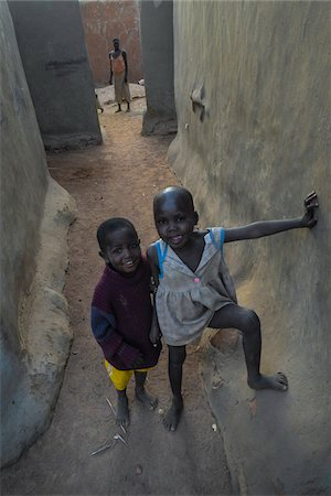 Two happy children standing in an alley with woman standing in the background, ebele Stock Photo - Rights-Managed, Code: 700-08171601