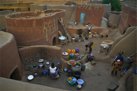 Traditional lifestyle of families on courtyards outside of homes, with modern little bike, Tiebele, Burkina Faso Stock Photo - Rights-Managed, Code: 700-08171619