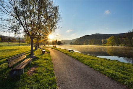 Cycle Path with Bench and Sun in the Morning on River Main, Collenberg, Churfranken, Spessart, Miltenberg-District, Bavaria, Germany Fotografie stock - Rights-Managed, Codice: 700-08231170