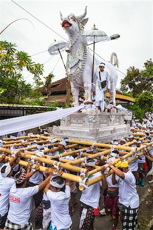 People carrying a raised, white bull character in a parade at a cremation ceremony for a high priest in Ubud, Bali, Indonesia Stock Photo - Rights-Managed, Code: 700-08385894