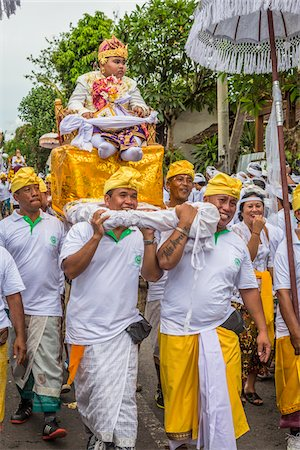 Boy being carried in a raised chair by people in a parade at a cremation ceremony for a high priest in Ubud, Bali, Indonesia Stock Photo - Rights-Managed, Code: 700-08385897
