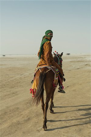 Nomad tribesman on horse back riding on the salt desert, Dordo, Kutch, Gujarat, India. Stock Photo - Rights-Managed, Code: 700-08416835
