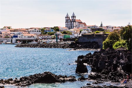 Strong surf crashes against the rocky lava coast in front of the city view with Church of Sao Mateus da Calheta, Sao Mateus da Calheta, Terceira Island, Azores, Portugal Stock Photo - Rights-Managed, Code: 700-08540021