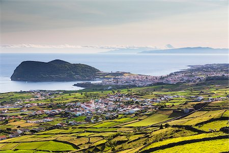 Agricultural land with lava stone walls in front of the view to Angra do Heroismo and the Volcano Monte Brasil, viewed from Serra da Ribeirinha, Terceira Island, Azores, Portugal Foto de stock - Con derechos protegidos, Código: 700-08540034