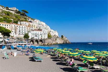 european hillside town - Tourists suntanning in lounge chairs with colorful sun umbrellas on the beach in front of Amalfi, Amalfi Coast, Italy Stock Photo - Rights-Managed, Code: 700-08639319