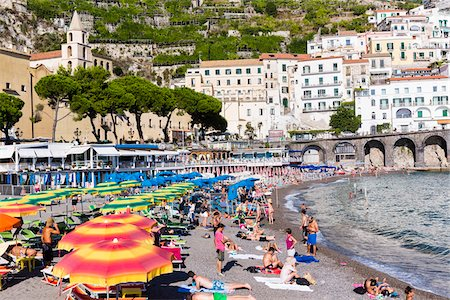 european hillside town - Tourists suntanning in lounge chairs with colorful sun umbrellas on the beach in front of Amalfi, Amalfi Coast, Italy Stock Photo - Rights-Managed, Code: 700-08639320