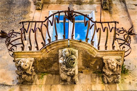 Baroque balcony railing with carved stone supports in Ragusa in Sicily, Italy Stock Photo - Rights-Managed, Code: 700-08723107