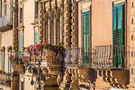Close-up of decorated balconies and shuttered windows on building in Ragusa in Sicily, Italy Stock Photo - Rights-Managed, Code: 700-08723114