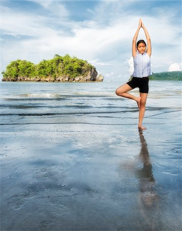 Thai girl doing a yoga position (tree pose) on Nopparat Thara Beach in Krabi Thailand. Stock Photo - Rights-Managed, Code: 700-08743683
