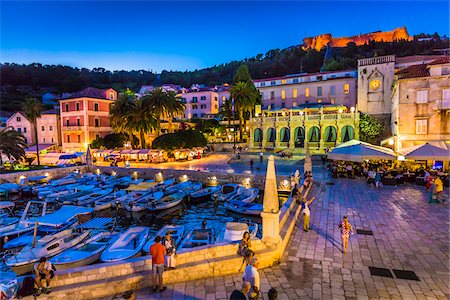 Boats docked at marina with the Venetian Loggia and the Hvar Fortress overlooking the harbour at dusk in the Old Town of Hvar on Hvar Island, Croatia Stock Photo - Rights-Managed, Code: 700-08765419