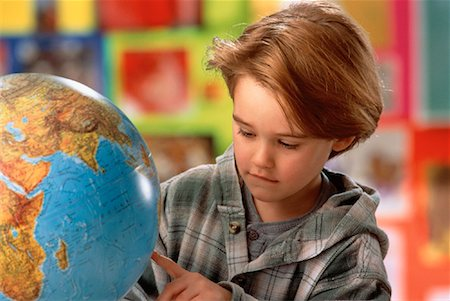 Boy in Classroom Looking at Globe Stock Photo - Rights-Managed, Code: 700-00017229
