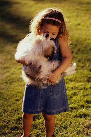dog kissing girl - Girl Standing in Field, Holding Dog Stock Photo - Rights-Managed, Code: 700-00036921