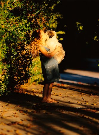 dog kissing girl - Girl Holding Dog Outdoors Stock Photo - Rights-Managed, Code: 700-00037205