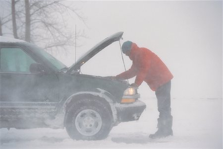Man Looking Under Hood of Vehicle Outdoors in Winter Stock Photo - Rights-Managed, Code: 700-00033485