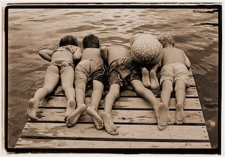 Back View of Children in Swimwear Looking over Edge of Dock Stock Photo - Rights-Managed, Code: 700-00041153