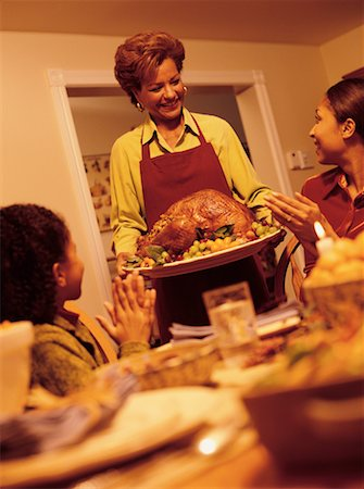 Grandmother Bringing Turkey to Thanksgiving Dinner Table Stock Photo - Rights-Managed, Code: 700-00055664