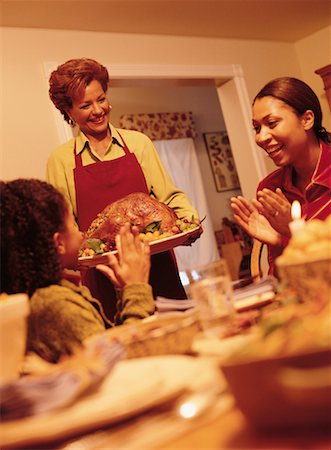 Grandmother Bringing Turkey to Thanksgiving Dinner Table Stock Photo - Rights-Managed, Code: 700-00055665
