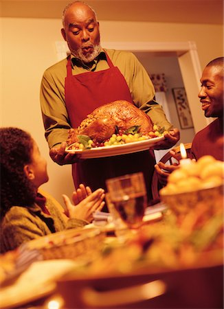 Grandfather Bringing Turkey to Thanksgiving Dinner Table Stock Photo - Rights-Managed, Code: 700-00055669