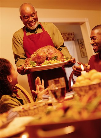Grandfather Bringing Turkey to Thanksgiving Dinner Table Stock Photo - Rights-Managed, Code: 700-00055670