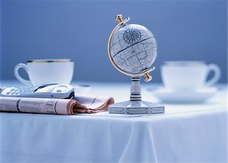 Small Globe, Newspaper, Cell Phone and Cups on Table Stock Photo - Rights-Managed, Code: 700-00056453