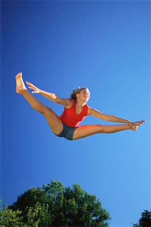Teenage Girl Jumping on Trampoline Outdoors Stock Photo - Rights-Managed, Code: 700-00069557