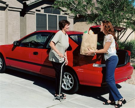 Daughter Handing Bag of Groceries To Mature Mother near Car Stock Photo - Rights-Managed, Code: 700-00062279