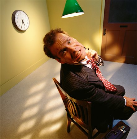 sweaty businessman - Worried Businessman Sitting in Chair Under Lamp Stock Photo - Rights-Managed, Code: 700-00063531