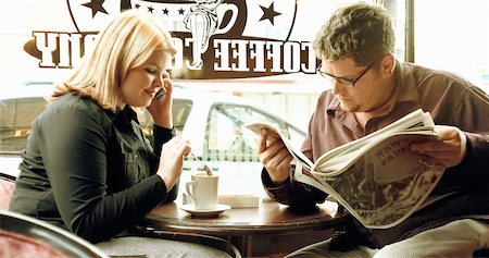 Couple Sitting in Cafe, Woman Using Cell Phone and Man Reading Newspaper Stock Photo - Rights-Managed, Code: 700-00085442