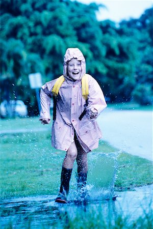 preteens shower - Child Running Through Puddle in Raincoat and Boots Stock Photo - Rights-Managed, Code: 700-00096488