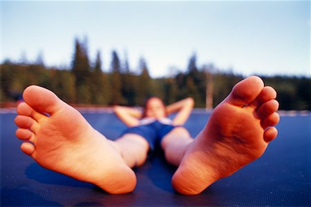preteen girl feet - Girl Lying on Trampoline Stock Photo - Rights-Managed, Code: 700-00188117