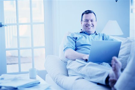 Man Using Laptop in Living Room Stock Photo - Rights-Managed, Code: 700-00193422