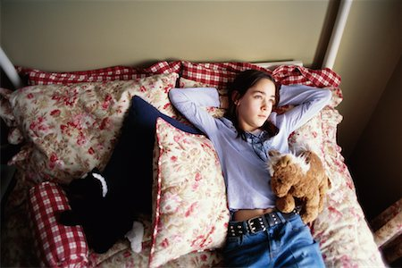 Teenage Girl Lying on Bed Stock Photo - Rights-Managed, Code: 700-00268959