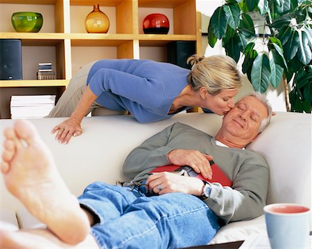 Man Resting on Sofa and Woman Kissing Him on Cheek Stock Photo - Rights-Managed, Code: 700-00343366