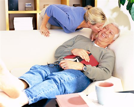Man Resting on Sofa and Woman Kissing Him on Cheek Stock Photo - Rights-Managed, Code: 700-00343367