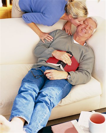 Man Resting on Sofa and Woman Kissing Him on Cheek Stock Photo - Rights-Managed, Code: 700-00343368