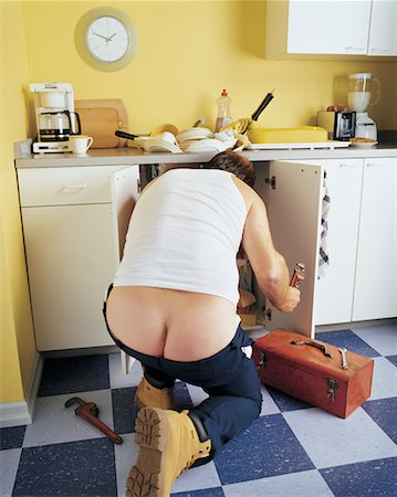 Back View of Plumber Working in Kitchen Stock Photo - Rights-Managed, Code: 700-00452654