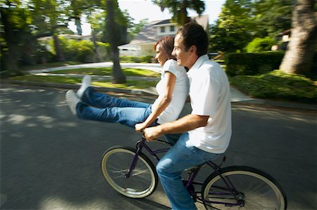 Couple Riding on Bicycle Together, Woman Sitting on Handlebars Stock Photo - Rights-Managed, Code: 700-00549931