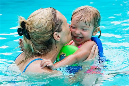 daughter kissing mother - Mother and Daughter Playing In Swimming Pool Stock Photo - Rights-Managed, Code: 700-00616878