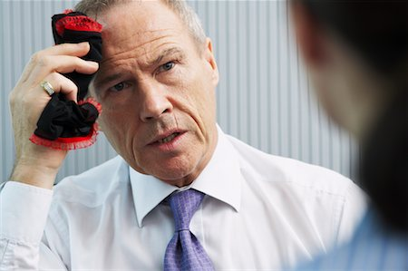 sweaty businessman - Businessman Wiping Forehead with Women's Underwear Stock Photo - Rights-Managed, Code: 700-00681421