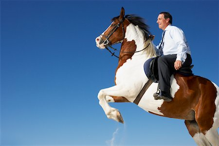Horse Rearing with Businessman on Its Back Stock Photo - Rights-Managed, Code: 700-01185194
