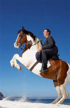 Horse Rearing with Businessman on Its Back Stock Photo - Rights-Managed, Code: 700-01185197
