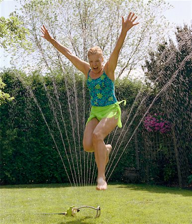 seniors woman in swimsuit - Mature Woman Jumping Through Sprinkler Stock Photo - Rights-Managed, Code: 700-01234774