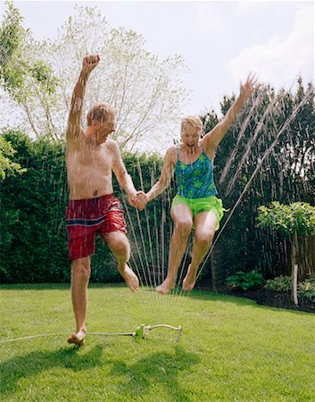 seniors woman in swimsuit - Mature Couple Jumping Through Spinkler Stock Photo - Rights-Managed, Code: 700-01234777