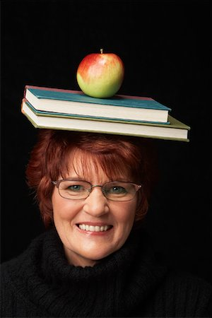 Woman Balancing Books and Apple on Her Head Stock Photo - Rights-Managed, Code: 700-01296562