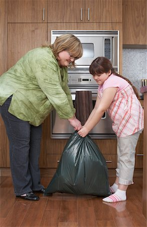 Mother and Daughter with Garbage Bag in Kitchen Stock Photo - Rights-Managed, Code: 700-01345078