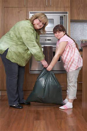 Mother and Daughter with Garbage Bag in Kitchen Stock Photo - Rights-Managed, Code: 700-01345079