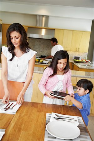 setting kitchen table - Family Setting Table Stock Photo - Rights-Managed, Code: 700-01579447