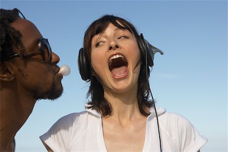 Man Blowing Bubble, Woman Listening to Music Stock Photo - Rights-Managed, Code: 700-01587322