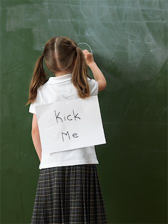 Girl Writing on Blackboard with Sign on Back Stock Photo - Rights-Managed, Code: 700-01646364
