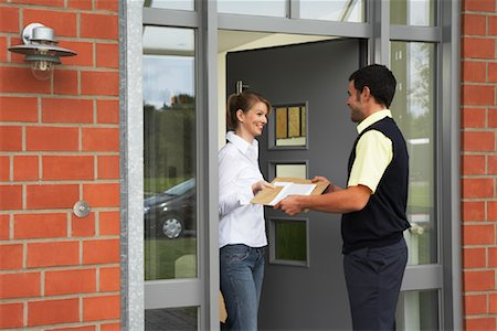 Delivery Person Giving Package to Woman Stock Photo - Rights-Managed, Code: 700-01716488